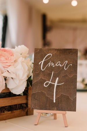 Number of a table on the wooden plate. Detail of a modern stylish wedding.
