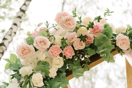 Beautiful flowers and roses of pastel color on a wedding arch. Details of a wedding decor for a ceremony