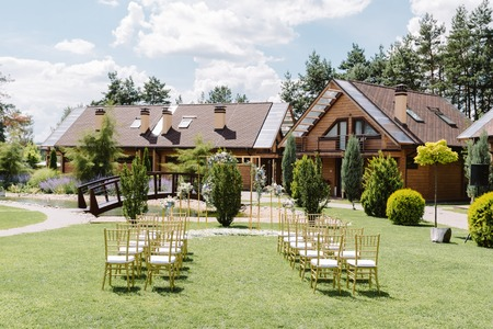 Stylish and modern decor for a wedding ceremony under the open sky. Wedding arch and beautiful chairs