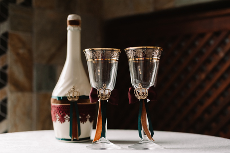 Wedding decorated champagne and glasses with the crown, green and red ribbons in the royal style