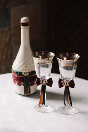 Wedding decorated champagne bottle and glasses with the crown, green and red ribbons in the royal style