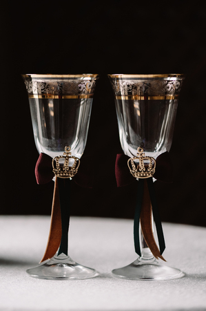 Wedding decorated champagne glasses with the crown, green and red ribbons in the royal style on the gark background