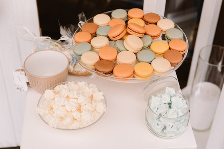 Beautiful wedding candy bar. Sweet products at a wedding. Beautiful tasty cookies and cakes on glasswares