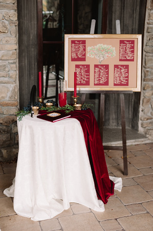 Wedding decoration of the board with the guests list near the table with white and red cloth in the castle of love