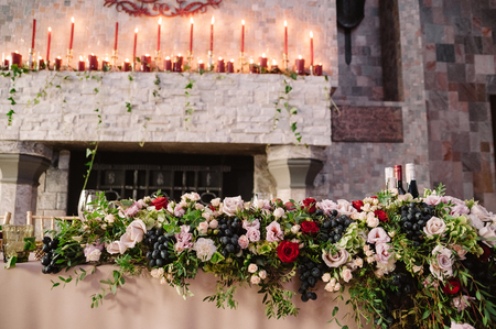 Wedding table decoration with the flowers, greenery, lighted candles for the fiance and fiancee