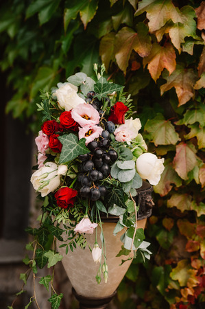 Wedding decorated vase with the red and pink flowers, grape and greenery for the ceremony