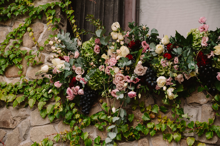 Wedding floral composition for the ceremony on the stone wall