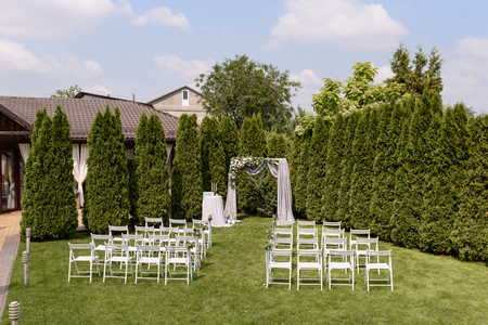 Wedding ceremony in white tints on a green lawn. 스톡 콘텐츠