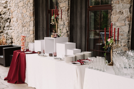 Wedding decoration of the table with red candles, candlesticks, white plates 스톡 콘텐츠