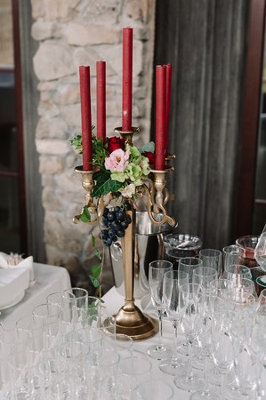 Wedding decorated candlestick with the vinous candles on the table