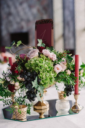 Wedding table decoration with the pink flowers, grape and greenery 스톡 콘텐츠