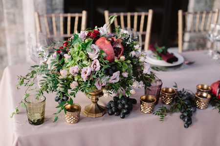 Wedding table decoration with the pink flowers, pomegranate and greenery 스톡 콘텐츠