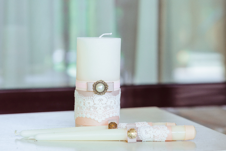 The white candles decorated with a tape with a brooch and lace.