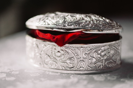 Wedding closed silver box with the rings and red rose petal