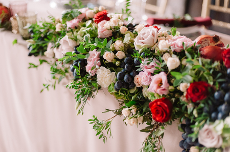 Wedding table decoration with the pink roses, grape and greenery