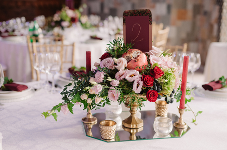 Wedding table decoration with the red, pink flowers and candles on the white cloth