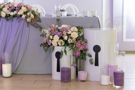 Big boxes with flowers. Candles in glass flasks on a parquet