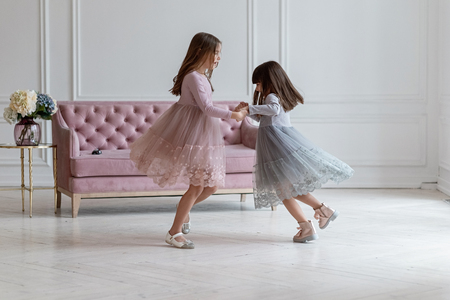 A cheerful game of amusing sisters in stylish dresses