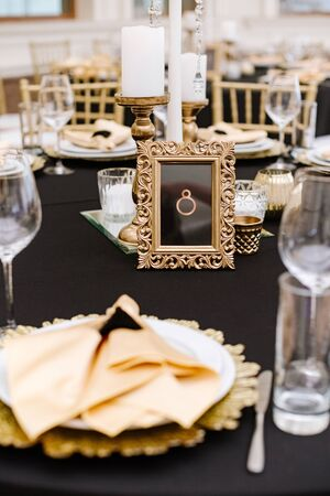 Guest table number in a golden carved frame on the dining table.