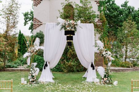 The square arch is decorated with white cloth, black chandelier and fresh flowers. Banque d'images - 132223794