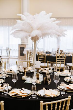 A tall pedestal with white feathers on the holiday table. Stylish decoration