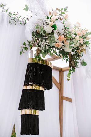 A black stylish chandelier and fresh flowers decorate the wedding arch. Original decor for stylish summer wedding