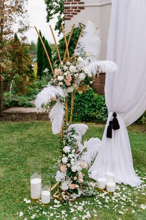 The original composition of metal details, feathers and live flowers in the decoration of the wedding ceremony. The modern stylish decor of an open-air wedding ceremony 스톡 콘텐츠