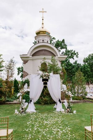A very stylish white wedding arch with unusual black decoration. Place for wedding ceremony Banque d'images - 132224158