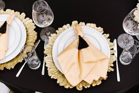 A dining white plate and a plate-decoration of golden metal on the table at the restaurant