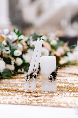 White wedding candles for the ceremony, decorated with an elegant pin and small black feathers.