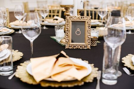 A rectangular frame with a table number stands on a stylish wedding table for guests.