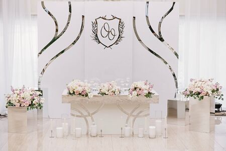 Luxurious wedding presidium in white with silver elements. Groom and bride s table decorated with beautiful flowers, candles a stylish white background
