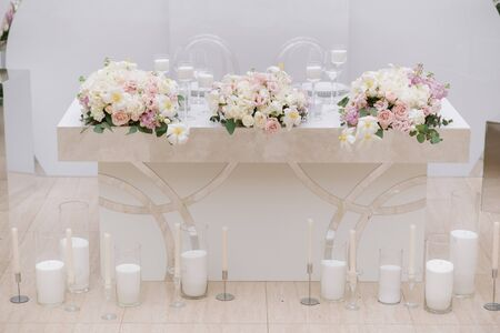 Stylish decor for a modern classic wedding. Beautiful wedding table is decorated with flowers and lots of candles.