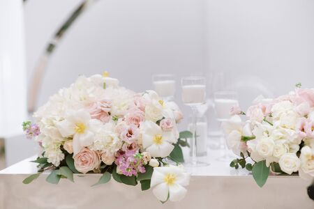 Stylish decoration of the modern wedding table with white candles and flowers in light shades. White candles and bouquet from an assortment of fresh and beautiful flowers decorate the festive table.