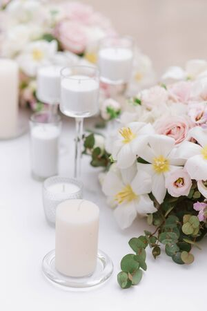 Stylish decoration of the wedding with flowers and candles in the style of minimalism. Elegant small bouquet of roses, greens and other colours on a white wedding table.