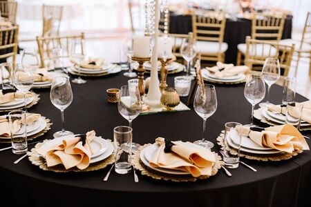 A black tablecloth, expensive utensils and gold details decorate the wedding table. The design of a classic wedding in a modern fashion style.