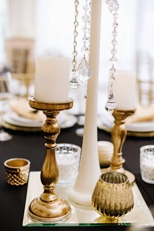 Tall golden candlesticks with white candles decorate the table at the event. Tiny stunning details decorating the space and table in the restaurant