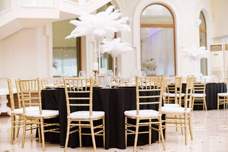 Stylish chairs and elegant gold-plated details. Black tablecloths on big, round tables for a wedding lunch. The luxurious design