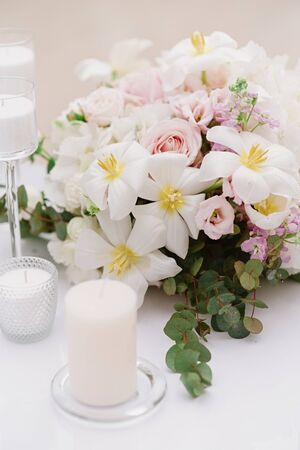 White candles and bouquet from an assortment of fresh and beautiful flowers decorate the festive table 스톡 콘텐츠