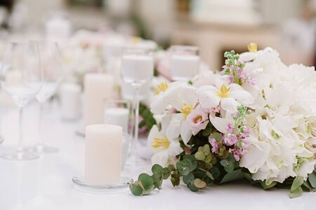 Luxury decoration of the wedding table with white candles and flowers in light shades