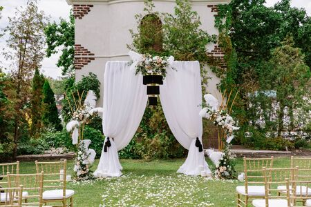 The square arch is decorated with aerial white cloth and stylish black chandelier Banque d'images - 132224376