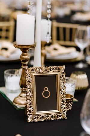 A rectangular gold frame with a table number stands on a stylish wedding table for guests.