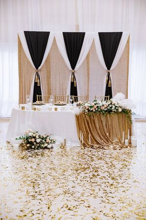 The grooms and brides table is decorated with candles, flowers, brilliant cloth in a classic luxury style. 스톡 콘텐츠