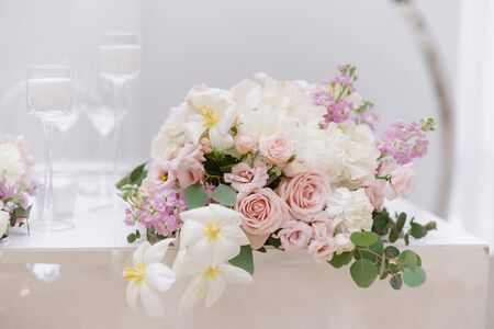 Elegant small bouquet of roses, greens and other colours on a white wedding table