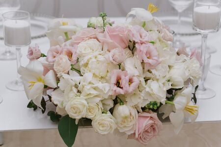 A large bouquet of light and pastel shades on the groom and bride s table. Beautiful white, pink fresh flowers 스톡 콘텐츠