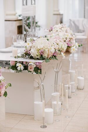 The groom and bride s beautiful wedding table is decorated with flowers and lots of different candles. 스톡 콘텐츠