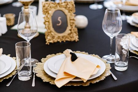 White and golden plates on black tablecloth. Beautiful service of wedding tables.