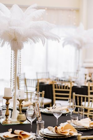 Stylish chairs and elegant gold-plated details. Black tablecloths on big, round tables for a wedding lunch.