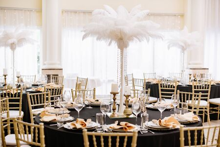 The restaurant hall with luxurious round tables decorated with bright and stylish decor is ready for reception.