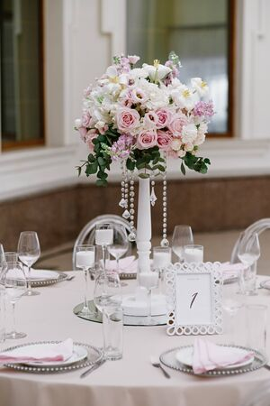 Wedding flowers on a tall white wooden stand decorate the festive table. Fashion design of the wedding in the style of minimalism.